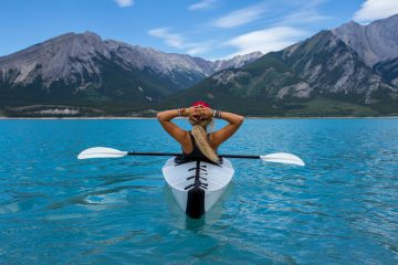 Effective managers take time to reflect and recharge. Kayaking woman with mountains.